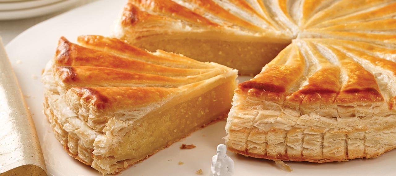 ガレット・デ・ロワというフランスの伝統的なパイ生地でできたアーモンドペーストの焼き菓子がお皿の上に乗っています。フェーヴと呼ばれる陶器でできた小さな人形がパイのそばに置かれています。