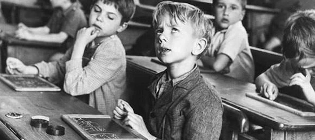 昔の時代に有名な写真家が撮ったモノクロ写真。教室にいる子供たちが机の上にそれぞれ小さな黒板をノートがわりに広げています。一人の男の子は一生懸命何かを考えていますが、隣の男の子は少しズルをして隣の子の答えを覗いているようです。