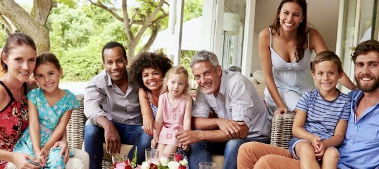 休日にリビングルームで楽しく過ごしているフランス人の家族9人。お父さんたち、お母さんたち、小学生くらいの子供たちがソファに腰掛けて楽しそうに笑っています。