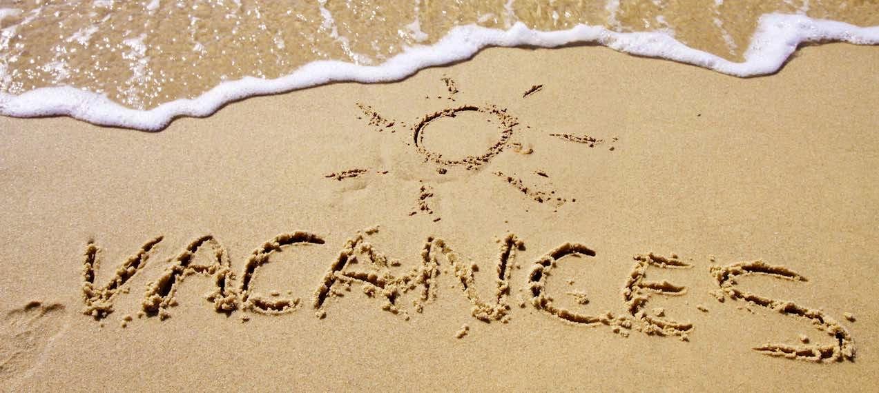夏の砂浜にアルファベットで書かれた「ヴァカンス」の文字とその上に描かれた太陽のイラスト。そこに打ち寄せる白い波。
