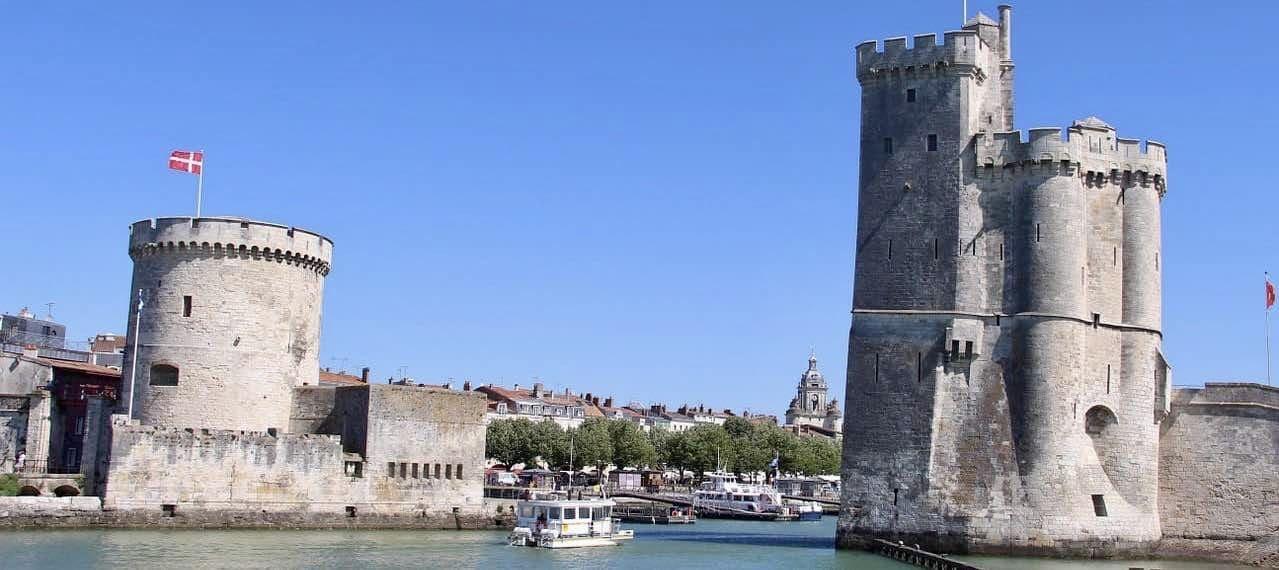フランスの西海岸のラロシェルという名前の美しい港。そこに中世で要塞として使われていた古い石造りの大きな建物があり、その間を海に続く運河が走り、その上を船が移動しています。港には他にもたくさんの船やヨットが停泊していて、向こう側に広がる丘には赤い煉瓦色の屋根の建物があります。