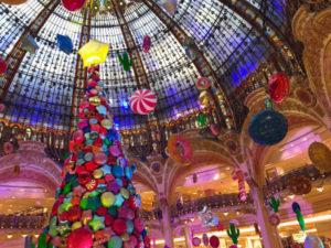 ギャラリー・ラファイエットのドーム状の建物の中に飾られている大きなクリスマスツリー。そこに飾りつけられているのはカラフルなオーナメントと、ツリーのてっぺんには大きな星の風船がついています。周りには星型が丸い形をしたカラフルな風船が沢山浮かんでいてドームの中がクリスマスの楽しい雰囲気になっています。