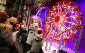 クリスマスになるとフランスのパリにあるギャラリー・ラファイエットのショーウィンドウがクリスマスをテーマにしたものになります。このショーウィンドウは遊園地をモチーフにしていて、小さな観覧車やジェットコースターやメリーゴーランドが中に飾られています。それを見ている小さな子どもたちとそのお母さんたちの様子。