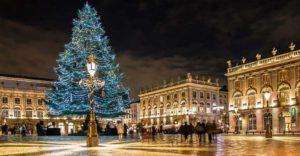 夜のフランスのクリスマスの風景。古い建築が広場の周りを囲い、その中心にライトアップされたクリスマスツリーがあります。ブルーのライトアップの光が暗い夜空にきらめいて綺麗な光景です。