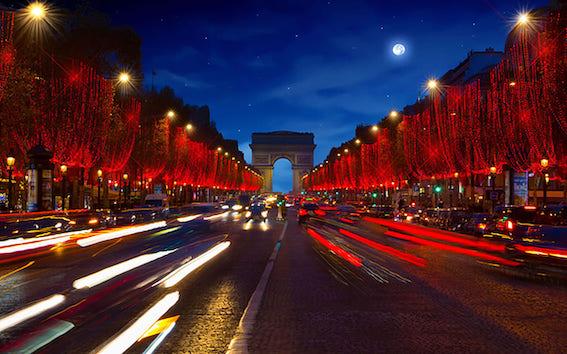 凱旋門へと続くパリのシャンゼリゼ通りの夜景。通りの両サイドに並ぶ樹々は美しい赤いイルミネーションで飾られていて、この通りを行き交う車のテールランプも赤く光り、夜空の深い青とのコントラストが美しいです。