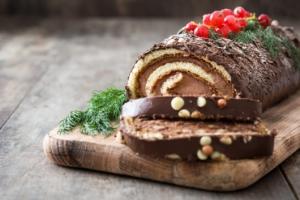フランスのブッシュ・ド・ノエルというクリスマスに食べる薪のモチーフのロールケーキ。中がスポンジケーキで、周りにチョコレートクリームがたっぷり塗られていて、上には赤い実や緑のもみの木の葉っぱを模した飾りがついています。端から2切れカットされていて切れ目のロールが見えて美味しそうです。