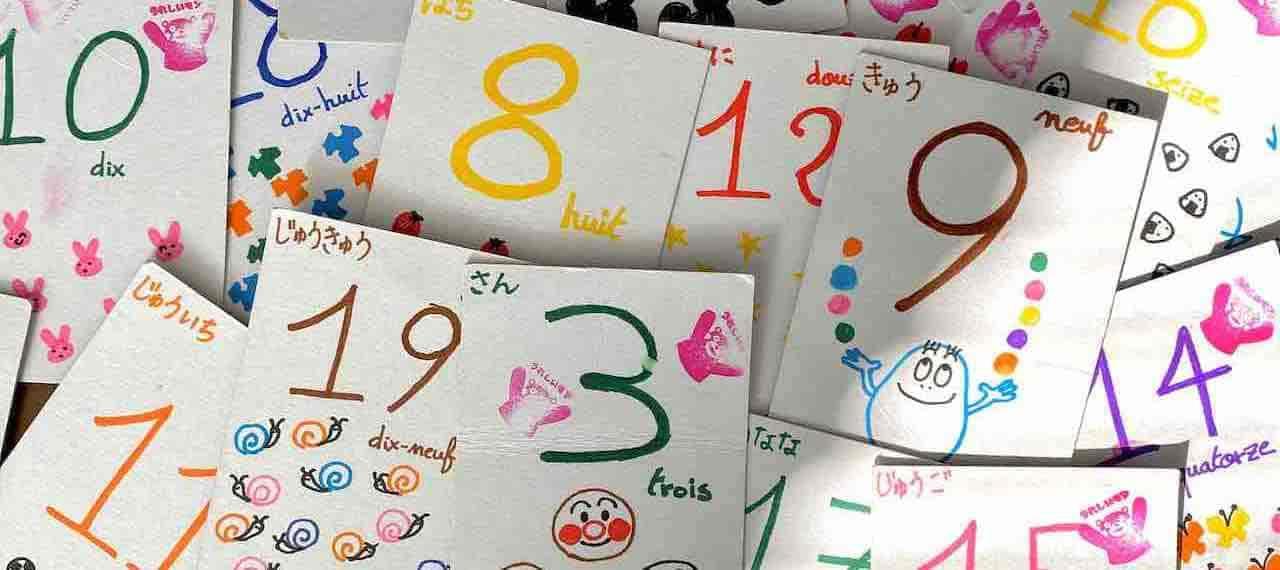 子共が数字を勉強するときのための数字のカード。いろいろな色で書かれた数字とかわいいイラストが1枚ずつ紙に描かれています。イラストはアンパンマンやバーバパパなどの有名なキャラクター。数字の読み方がフランス語と日本語の両方で書かれています。