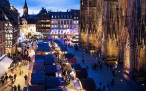 フランスのストラスブールの夜のクリスマスマーケットの賑わいの様子。ストラスブールの大きなカテドラル前の広場に、沢山の小さなお店がひしめいて並び、人々が集まってきています。広場の周りの建物にもイルミネーションが飾られて明るく楽しげなムードです。
