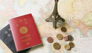 世界地図のヨーロッパ地域の上に、エッフェル塔のレプリカと様々な種類のユーロのコインが置いてあり、その横に赤と濃紺の日本のパスポートが置かれている様子。